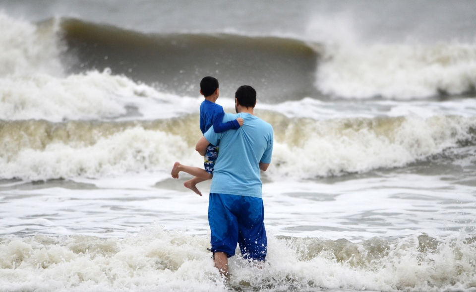 Beach goers watch waves generated by Hurricane Sandy along a breezy Coligny Beach Park on Hilton Head Island, S.C., on Saturday, Oct. 27, 2012.  (AP / The Island Packet, Jay Karr)