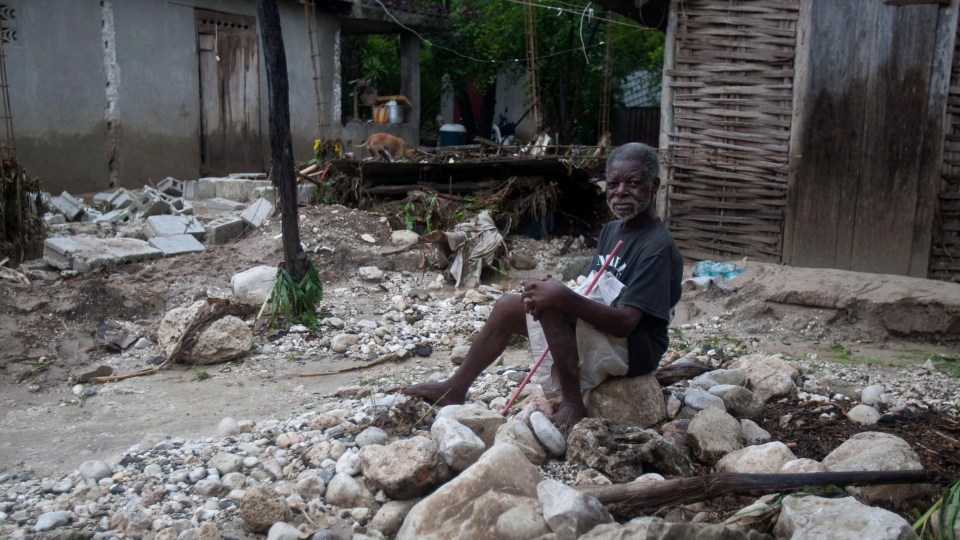 A man sits in front of his home, on debris left by a flood caused by the heavy rains from Hurricane Sandy in Gran Goave, Haiti on Friday, Oct. 26, 2012.  (AP / Dieu Nalio Chery)