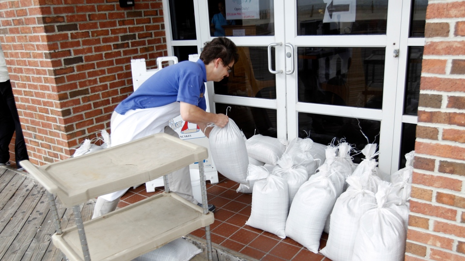 A restaurant worker piles sand bags at the entrance of the business as Hurricane Sandy approaches the Atlantic Coast, in Ocean City, Md., on Saturday, Oct. 27, 2012. ( AP / Jose Luis Magana)