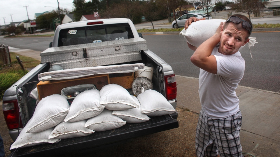 Nick Almeter, 26, prepares for Hurricane Sandy, as he carries a sandbag to place by properties along Ocean View Avenue, in Norfolk, Va., Saturday, Oct. 27, 2012  (AP / The Virginian-Pilot, Ross Taylor)
