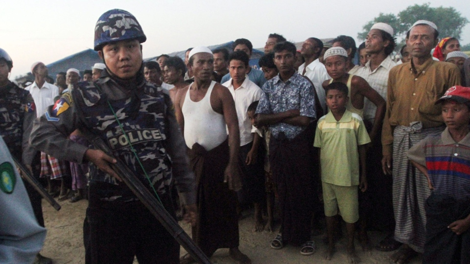 An armed police officer guards stands with Muslim refugees at a refugee camp in Sittwe, capital of Rakhine State, western Myanmar, Saturday, Oct. 27, 2012. (AP Photo/Khin Maung Win)