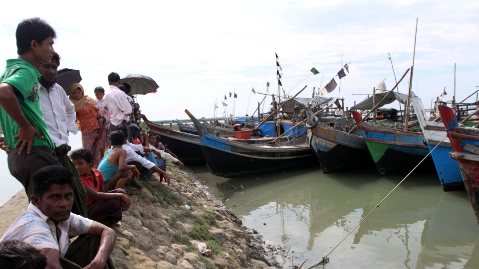 People gather and watch boats with refugees on board arrive in Sittwe, Rakhine State, western Myanmar on Sunday, Oct. 28, 2012. (AP / Khin Maung Win)