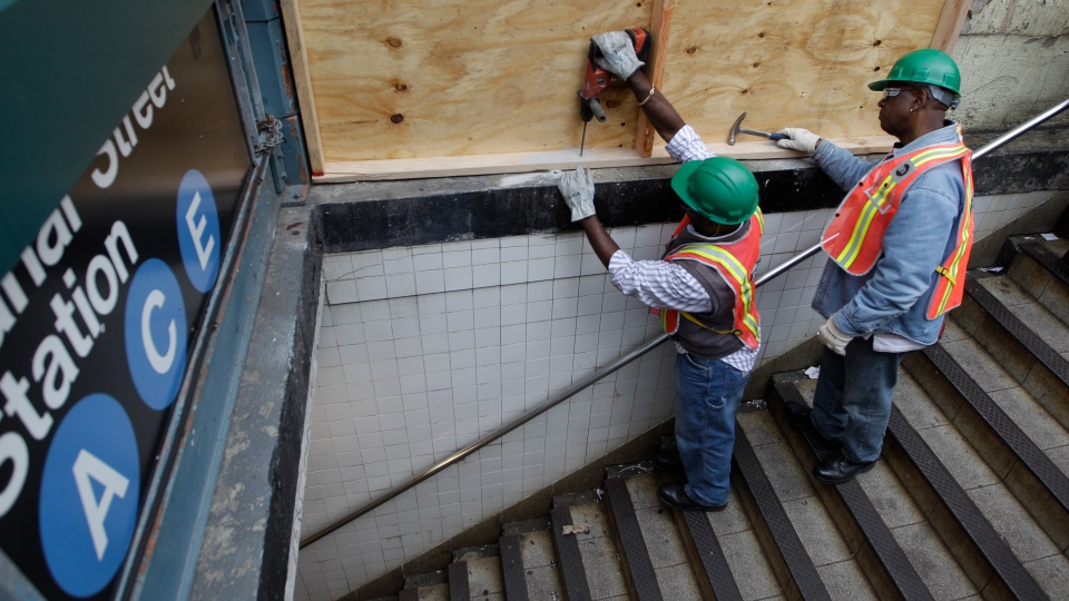 Metropolitan Transportation Authority workers cover an entrance to the Canal Street A, C, and E station with plywood to help prevent flooding, Saturday, Oct. 27, 2012, in New York. (AP / Mary Altaffer)