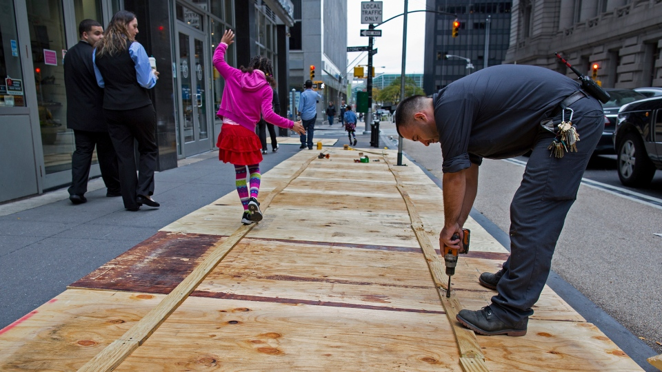 A maintenance worker named Vitto attaches plywood to a sidewalk grate at the 2 Broadway building of Lower Manhattan in New York on Sunday, Oct. 28, 2012. (AP / Craig Ruttle)