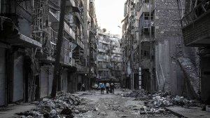 Syrian residents walk on a street among the debris of buildings damaged by heavy shelling in the southeast of Aleppo City, Saturday, Oct. 27, 2012. (AP / Narciso Contreras)