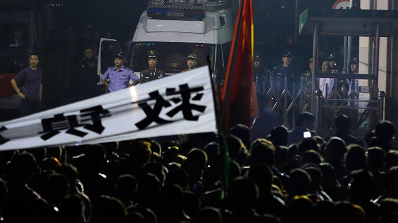 Chinese security personnel guard the entrance to the city government office where residents gathered to protest the expansion of a petrochemical factory in Zhejiang province's Ningbo city, Sunday, Oct. 28, 2012.  (AP / Ng Han Guan)