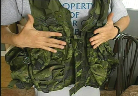 Cpl. Daniel Beaulieu demonstrates how the soldiers' vests don't have enough pockets to hold the ammunition that they should have.