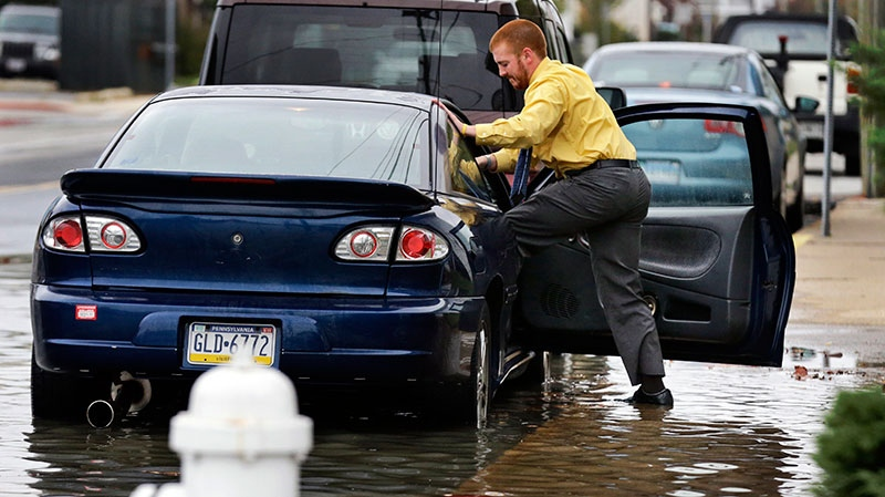 Cody Billotte walks through the high water as he loads his car to go to work in Ocean City, Md., as Hurricane Sandy bears down on the East Coast, Sunday, Oct. 28, 2012.  (AP / Alex Brandon)