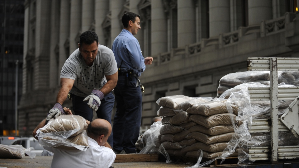 Sandbags are off loaded for placement in front of No. 2 Broadway in Battery Park in preparation of the storm in New York, Sunday, Oct. 28, 2012. (AP / Louis Lanzano)