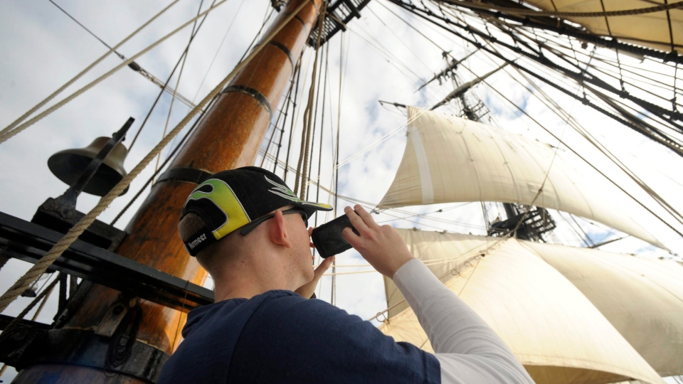 Petty Officer 3rd class Zachary Mullins snaps photos of crewmates, high in the rigging of the square rigged sailing ship HMS Bounty off New London, Conn. on Thursday, Oct. 25, 2012. (The Day / Sean D. Elliot)