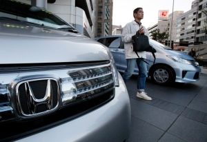 A man walks by Honda vehicles displayed in front of Honda Motor Co. headquarters in Tokyo Monday, Oct. 29, 2012. (AP / Koji Sasahara)