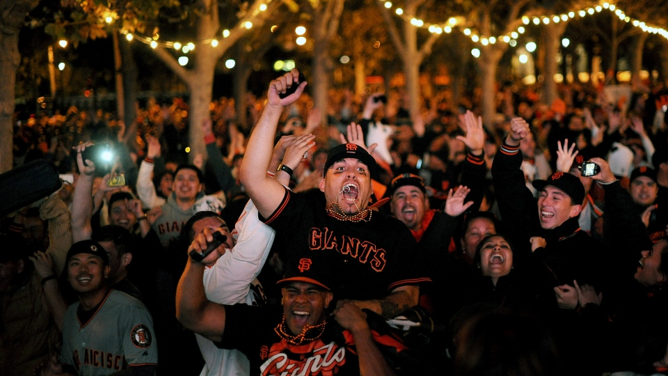San Francisco Giants fans celebrate outside San Francisco's City Hall while watching a broadcast of the Giants facing the Detroit Tigers in Game 4 of baseball's World Series on Sunday, Oct. 28, 2012. The Giants won the game 4-3 to sweep the series. (AP Photo/Noah Berger)