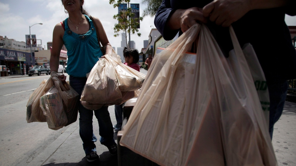 Two women wait for a bus after their grocery shopping in Los Angeles, Thursday, May 24, 2012. (AP / Jae C. Hong)