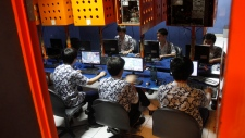 Indonesian students browse at an internet cafe