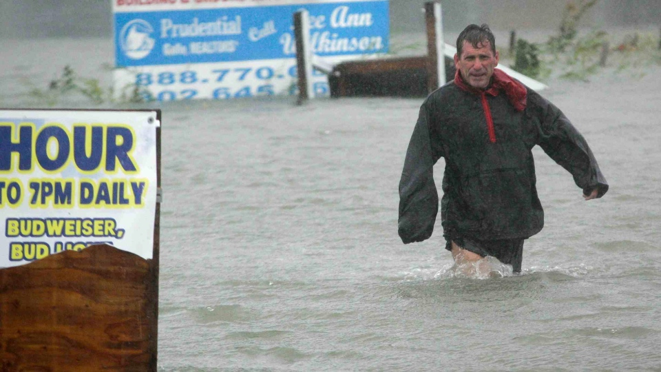 After checking to make sure his boat line is secure, Bob Casseday crosses the waist high flooded street just over the bridge along Savannah Road as Hurricane Sandy hits in Lewes, Del.,  Monday, Oct. 29, 2012. (The Wilmington News-Journal / Suchat Pederson)