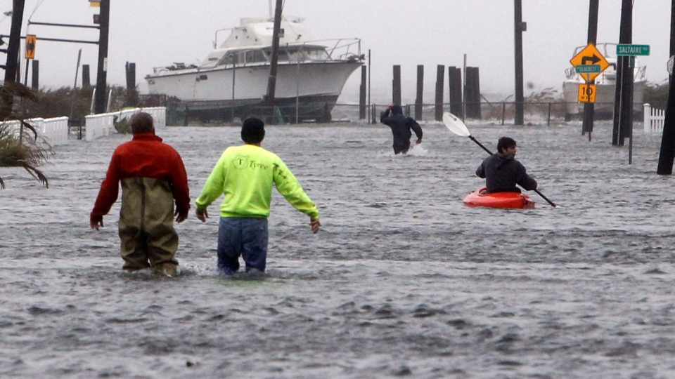 People wade and paddle down a flooded street in Lindenhurst, N.Y. , Monday, Oct. 29, 2012. (AP / Jason DeCrow)