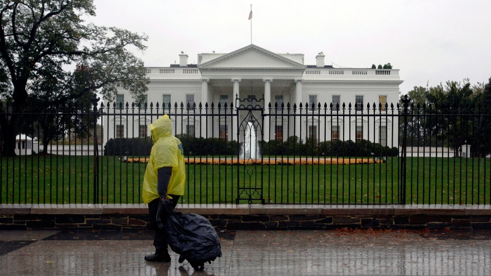 A lone man wearing a rain pouch walks past the White House in Washington during the approach of Hurricane Sandy, Monday, Oct. 29, 2012. (AP / Jacquelyn Martin)