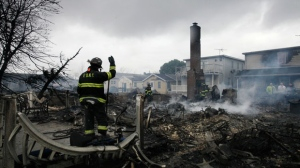 A fire fighter surveys the smoldering ruins of a house in the Breezy Point section of New York on Tuesday, Oct. 30, 2012. (AP / Mark Lennihan)