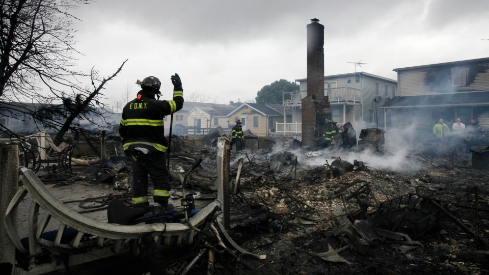 A fire fighter surveys the smoldering ruins of a house in the Breezy Point section of New York, Tuesday, Oct. 30, 2012.  (AP / Mark Lennihan)