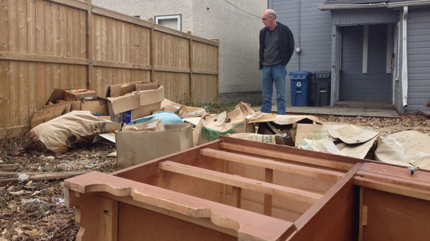 Adrian Peters looks on at trash that has been illegally dumped on a property he owns. (File image)