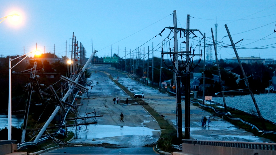 Downed power lines and a battered road is what superstorm Sandy left behind as people walk off the flooded Seaside Heights island on Tuesday, Oct. 30, 2012. (AP /Julio Cortez)