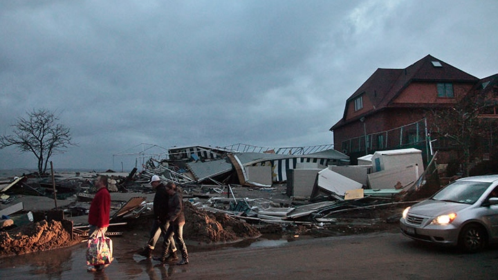 People walk through the houses destroyed in the aftermath of yesterday's storm surge from superstorm Sandy, Tuesday, Oct. 30, 2012, in Coney Island's Sea Gate community in New York. (AP / Bebeto Matthews)