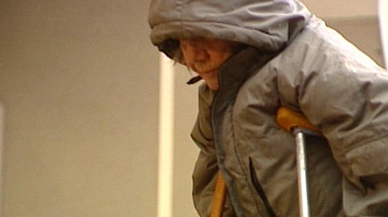 Anne Semenovich, 74, slowly makes her way into the courthouse Monday morning, supported by crutches.