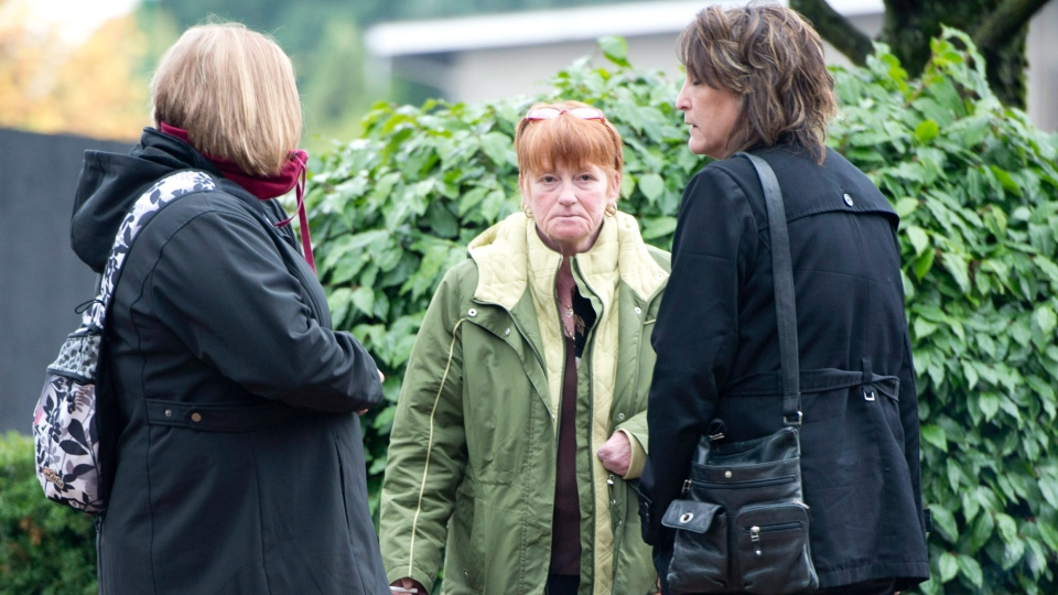Lela Phillips (centre) is seen outside the Coroner's Court in Burnaby, B.C. Tuesday, Oct. 30, 2012. (Jonathan Hayward / THE CANADIAN PRESS)