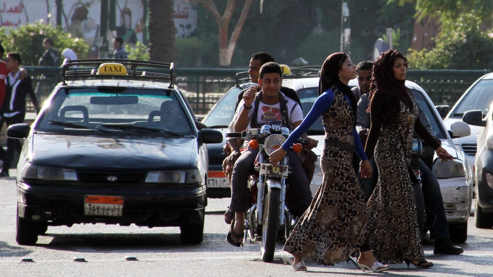 A youth on a motorcycle watches as young girls walk past near Cairo's Tahrir Square, Sunday, Oct. 28 2012. (AP / Mohammed Abu Zeid)