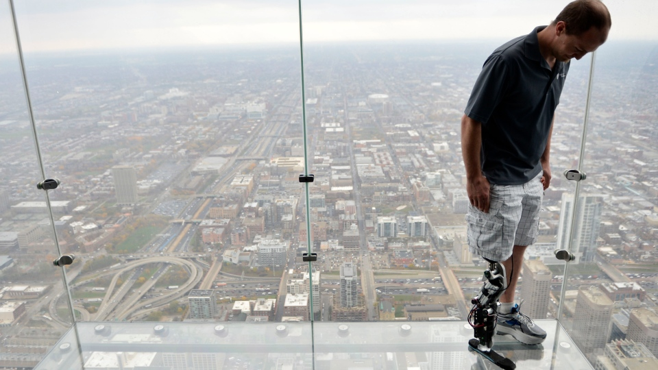 "Zac Vawter, fitted with an experimental ""bionic"" leg, looks down from the Ledge at the Willis Tower in Chicago, Oct. 25, 2012. (AP / Brian Kersey)"