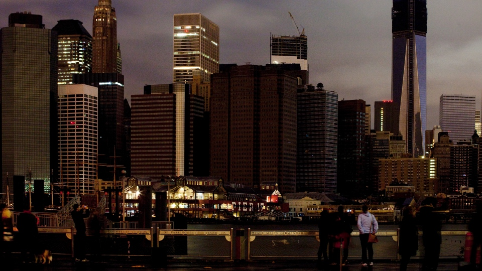 People look across the East River from Brooklyn into lower Manhattan, where some buildings were operating with emergency backup generators in New York, Tuesday, Oct. 30, 2012. (AP / Mark Lennihan)