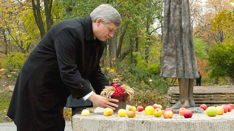 Prime Minister Stephen Harper places a jar of grain at the 'Sad Memory of Childhood' at the Holodomor Monument in Kyiv, Ukraine on Monday, Oct. 25, 2010. (Sean Kilpatrick /  THE CANADIAN PRESS)
