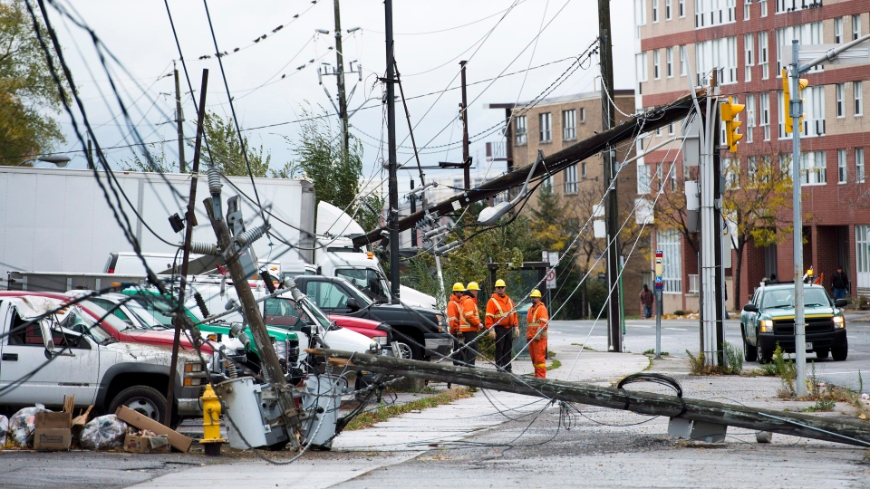Toronto hydro workers overlook the damage in Toronto on Tuesday, Oct. 30, 2012. (Nathan Denette / THE CANADIAN PRESS)