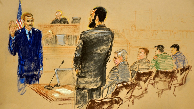 In this photo of a sketch by courtroom artist Janet Hamlin and reviewed by a U.S. Department of Defense official Capt Michael Grant, USAF swears in Omar Khadr, right, at the Camp Justice compound of Guantanamo Bay U.S. Naval Base in Cuba, Monday, Oct. 25, 2010.