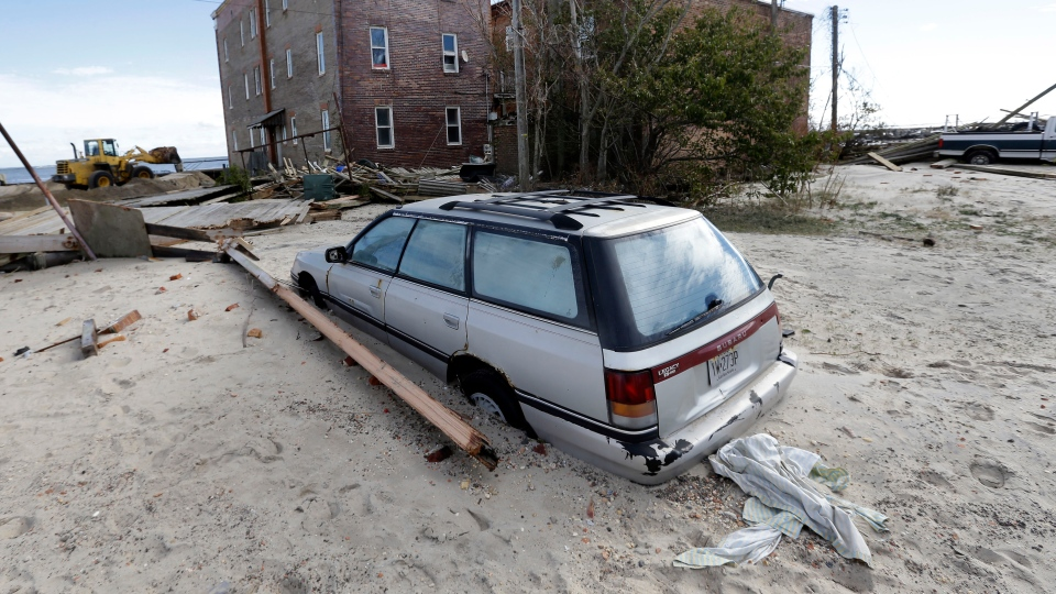 A car is partially buried by sand that was washed ashore by superstorm Sandy in Atlantic City, N.J., Wednesday, Oct. 31, 2012. (AP / Patrick Semansky)