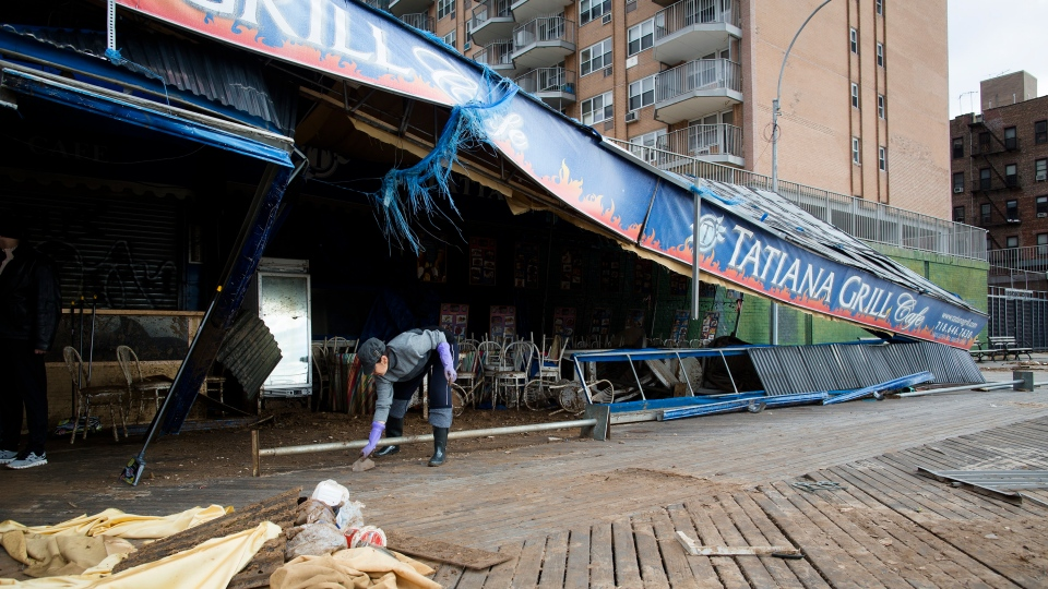A worker picks up debris outside of the damaged Tatiana Grill on the Brighton Beach boardwalk in the Brooklyn borough of New York, Wednesday, Oct. 31, 2012. (AP / John Minchillo)
