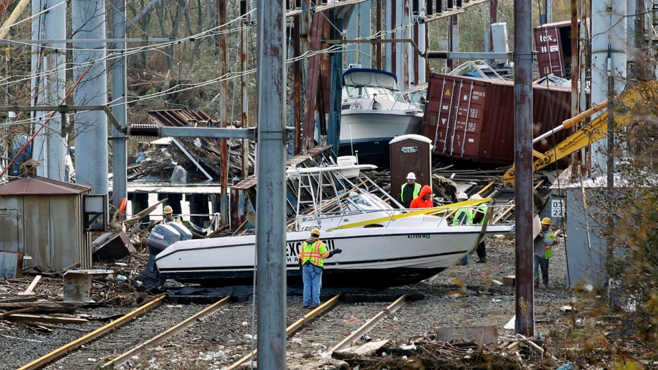 Workers try to clear boats and debris from the New Jersey Transit's Morgan draw bridge Wednesday, Oct. 31, 2012, in South Amboy, N.J., after Monday's storm surge from Sandy pushed boats and cargo containers onto the train tracks. (AP / Mel Evans)