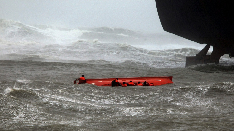 Sailors try to hold on to their up-turned lifeboat, as sailors, not pictured, throw lines to them from the ship above, after the lifeboat capsized when Indian ship Pratibha Cauvery, right, ran aground, due to strong winds in the Bay of Bengal coast in Chennai, India, Wednesday, Oct. 31, 2012. (AP Photo)