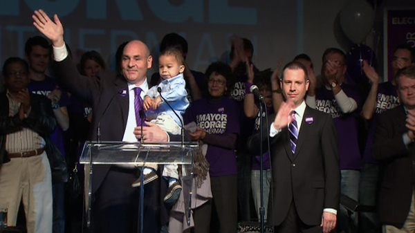 George Smitherman holds his son Michael as his husband Christopher, right, looks on during the concession speech in Toronto, Monday, Oct. 25, 2010.