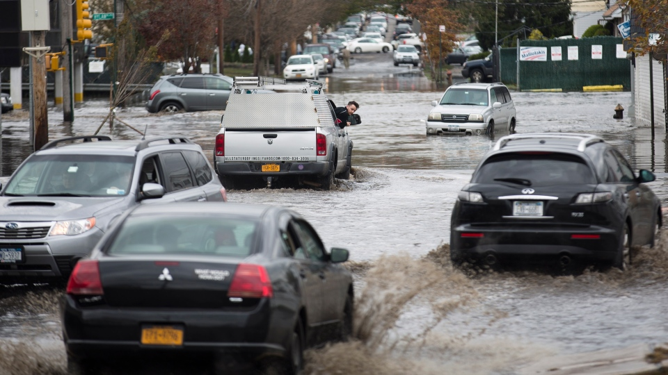 A passenger inspects the water level around his vehicle as multiple cars drive through a flooded street in the Staten Island borough of New York on Wednesday, Oct. 31, 2012. (AP / John Minchillo)
