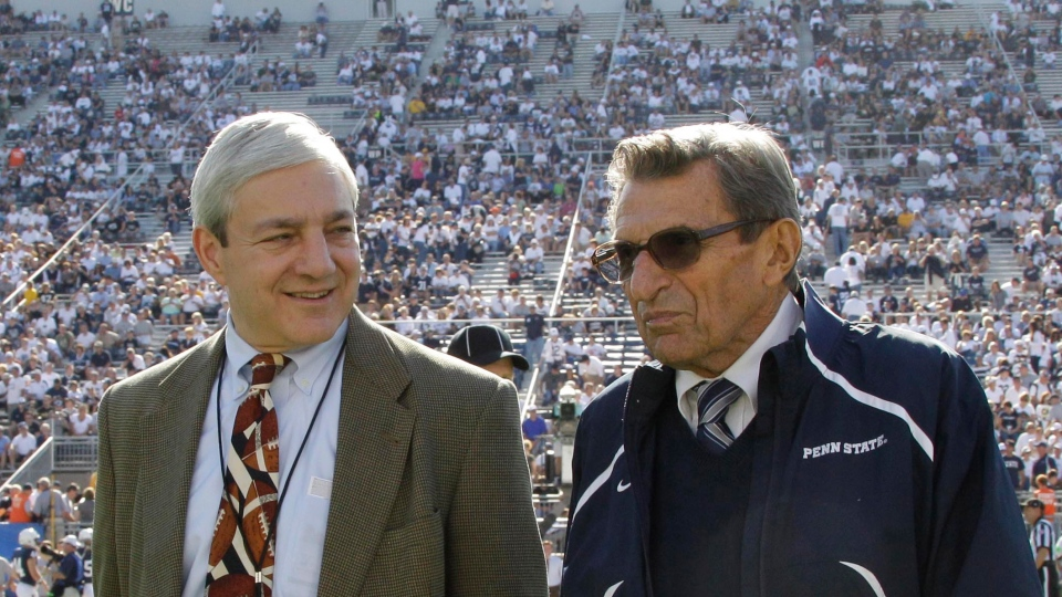 Former Penn State president Graham Spanier, left, and head football coach Joe Paterno talk before an NCAA college football game against Iowa in State College, Pa., in this October 2011 file photo. (AP / Gene Puskar)