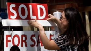 A real estate agent puts up a 'sold' sign in front of a house in Toronto on Tuesday, April 20, 2010. (Darren Calabrese / THE CANADIAN PRESS)