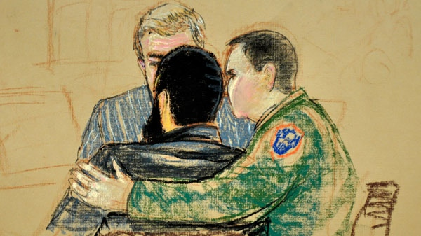 In this photo of a sketch by courtroom artist Janet Hamlin and reviewed by a U.S. Department of Defense, Canadian Omar Khadr, center, is embraced by Pentagon-appointed military defense lawyer Army Lt. Col. Jon Jackson, right, as his Canadian lawyer Dennis Edney looks on during Khadr's trial at the Camp Justice compound of Guantanamo Bay U.S. Naval Base in Cuba, Tuesday Oct. 26, 2010. (AP /Janet Hamlin, Pool)