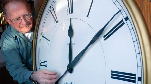 This file photo shows Pat Boyden, owner of the Green Mountain Clock Shop in Williston, Vt., as he sets the time forward in preparation for daylight saving time. (AP Photo/Rob Swanson, FILE)