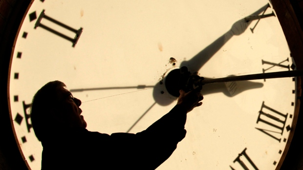Custodian Ray Keen checks the time on a clock face after changing the time on the 97-year-old clock atop the Clay County Courthouse, in this Nov. 6, 2010 file photo taken in Clay Center, Kan. (AP Photo/Charlie Riedel)
