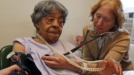 This Oct. 13, 2009 photo shows Dr. Linda Abbey, right, listening to the heartbeat of 103 year old Nannie Sutton, as her blood pressure is taken in Richmond, Va. (AP Photo/Steve Helber)