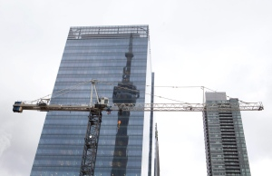 The CN tower is reflected in a high rise building behind a construction crane in downtown Toronto on Saturday, February 4, 2012.(THE CANADIAN PRESS / Pawel Dwulit)