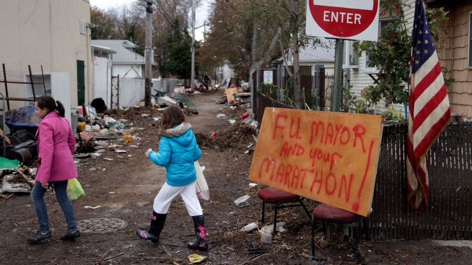 A sign about the marathon and New York City Mayor Michael Bloomberg is displayed in a devastated section of Staten Island, New York, Friday, Nov. 2, 2012.  (AP / Seth Wenig)