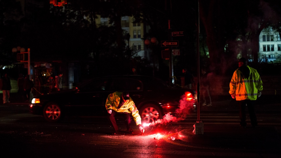 A NYPD traffic officer lights a flare to illuminate a darkened street at Union Square whose power has been offline due to damage caused by Superstorm Sandy, Friday, Nov. 2, 2012, in New York. (AP / John Minchillo)