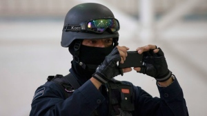 In this file photo, a federal police officer takes pictures with a cell phone in Mexico City on Thursday, Sept. 6, 2012. (AP / Eduardo Verdugo)